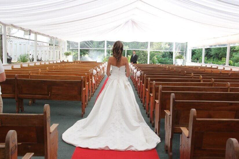 Mariée descend l'allée de la chapelle extérieure